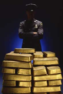 Man guarding gold bars